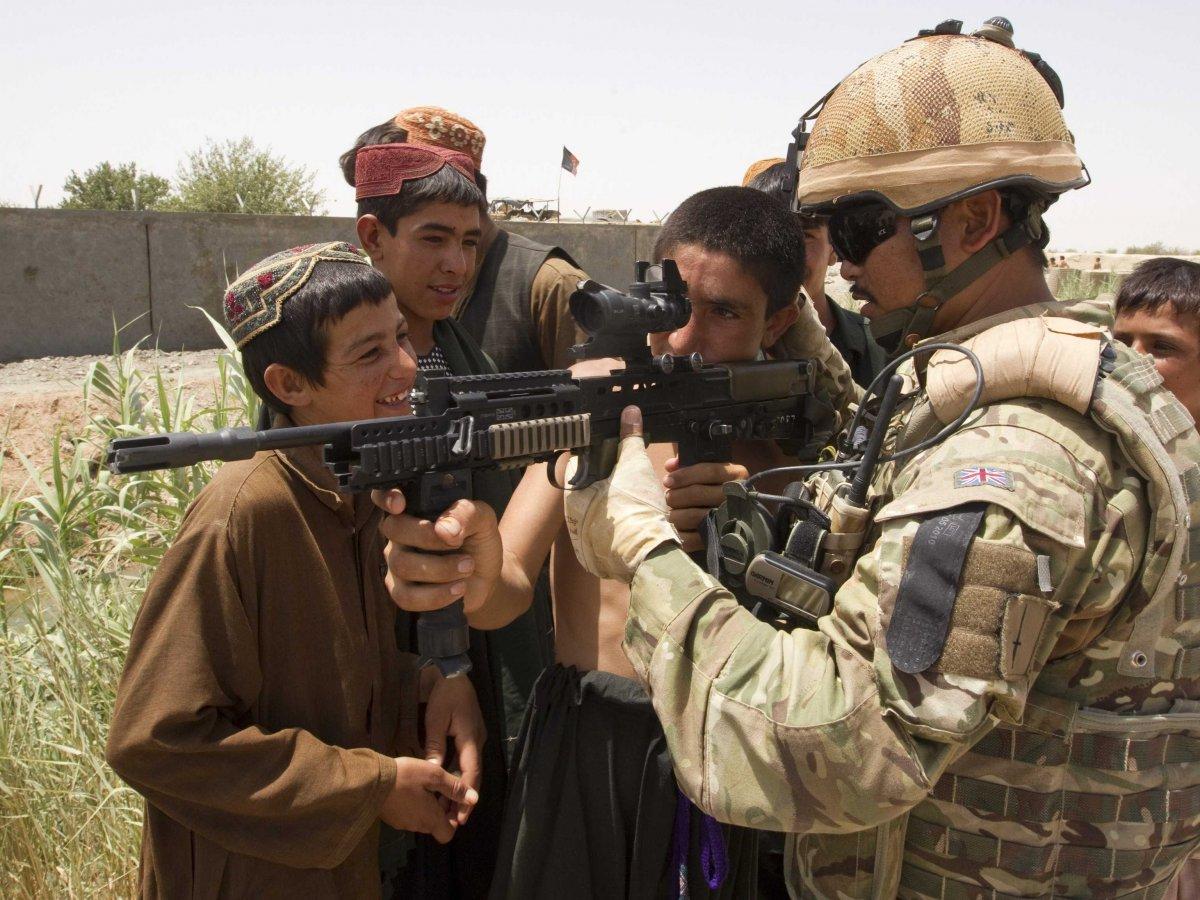 British army Cpl. Birendra Limbu of the 2nd Battalion, Royal Gurkha Rifles shows his rifle to Afghan children.(Shamil Zhumatov/REUTERS)