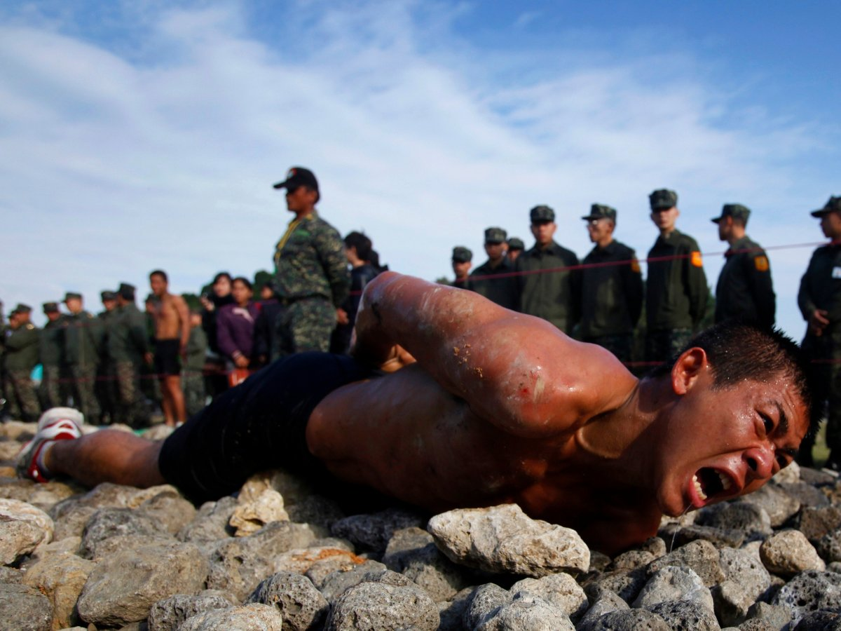 """A trainee leopard-crawls along a 50-meter-long path of jagged coral and rocks as part of the Taiwan marines' frogmen """"Road to Heaven"""" test in Zuoying, Kaohsiung, on January 19, 2011.(Nicky Loh/REUTERS)"""